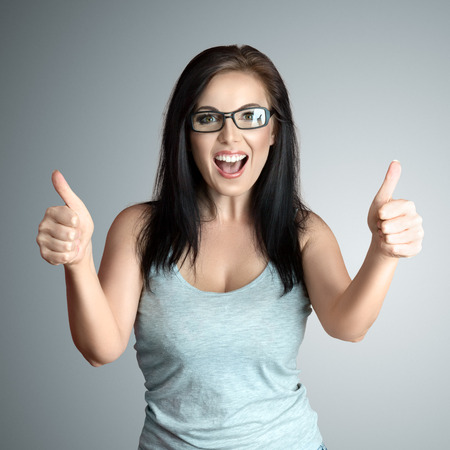Happy woman showing thumbs up gesture good or ok photo
