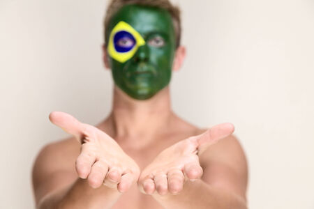 Soccer fan with brazil flag painted over face showing open hands photo