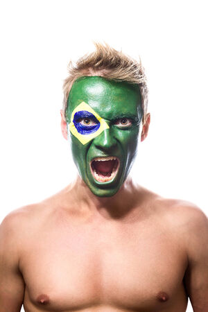 brazilian flag: Soccer fan with brazil flag painted over face Stock Photo