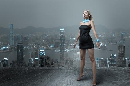 未来的なファッションの女性の夜香港の街の景観に小さな黒いドレスでポーズ