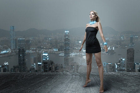Futuristic fashion woman posing in small black dress at cityscape of night hongkong city Stockfoto