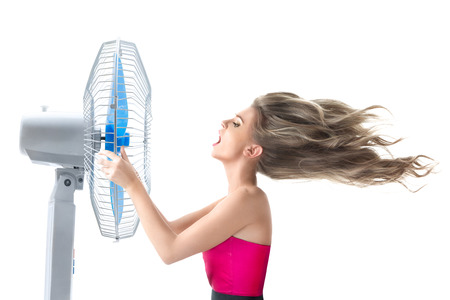 Young woman cooling face under wind of cooler fan isolated on white background photo