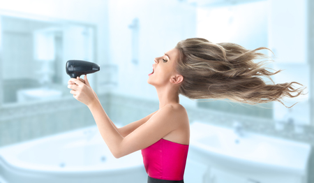Young blonde woman drying her long hair with electric fan photo