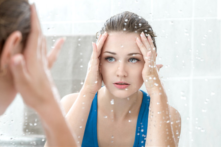girls bathing: Young woman washing her face with clean water in bathroom