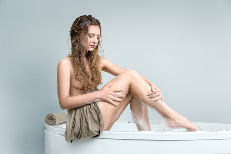 lying in bathtub: Young beautiful woman washing legs in a bath Stock Photo