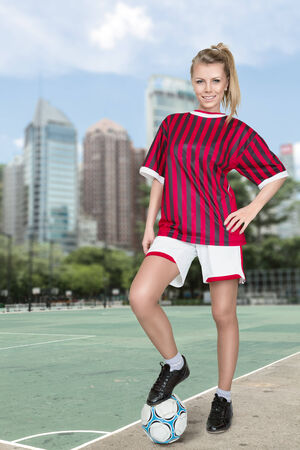 Young blonde woman posing with footbal ball in front of city view photo