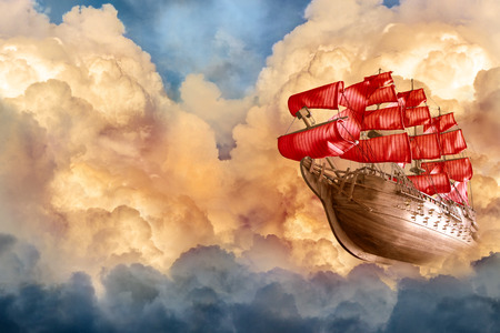 Romantic sailing ship flying in sunset clouds photo