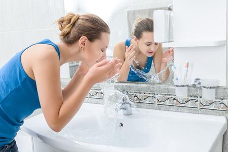 lavar: Mujer joven que se lava la cara con agua limpia en el baño