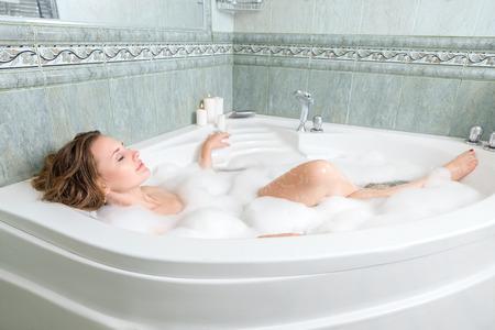 mujer bañandose: Mujer hermosa joven relajante en un baño Foto de archivo