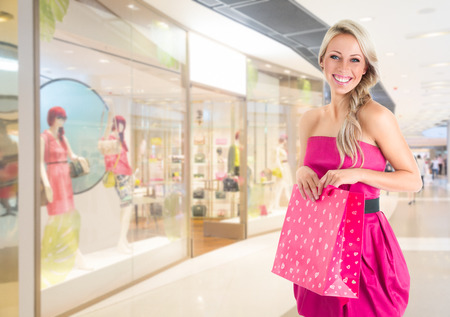 Young beautiful woman in pink mini dress at shopping mall photo