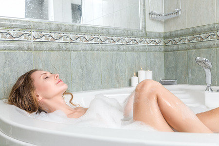 Young beautiful woman relaxing in a bath Stock Photo