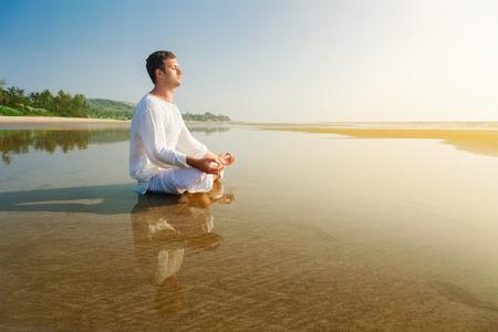 Hombre que hace asana de yoga, meditando en posición de loto Foto de archivo