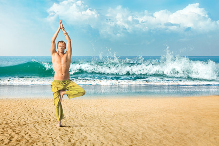 Young man doing yoga and meditating in tree position at sea beach