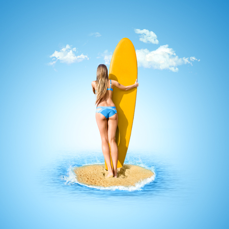 Young woman looking at tropical sea with sufboard in hands. Rear view outdoor photo