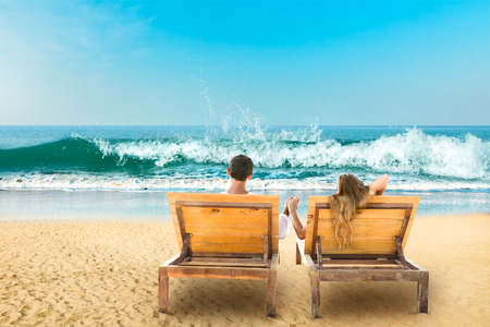 Young couple relaxing lying down on a beach chair photo