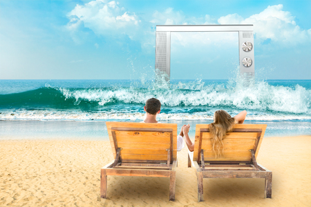 hd tv: Young couple relaxing lying down on a beach chair and watch tv