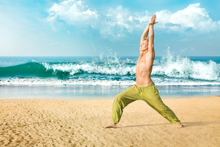 Young man doing yoga and meditating in warrior pose at sea beach