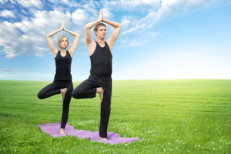 tree position: Man and woman doing yoga meditating in tree position