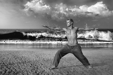 Young man doing yoga and meditating in warrior pose at sea beach photo