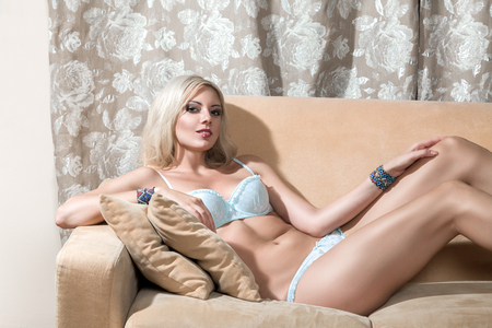 Young beautiful woman in lingerie lying on a vintage sofa photo