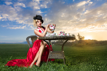 Young woman posing as magnificent card queen from wonderland at mystic tea-party Standard-Bild