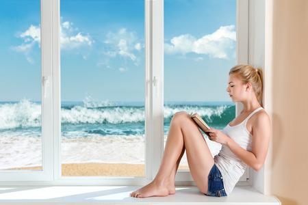 Young woman read book sitting on windowsill photo