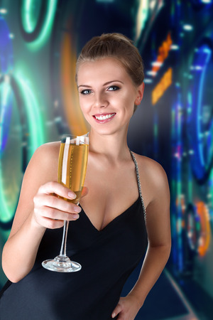 Beautiful young woman with glass of champagne in hands against illuminated background photo
