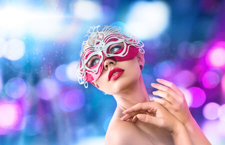 masquerade mask: Young woman in mysterious venetian carnival red mask in front of night city illumination
