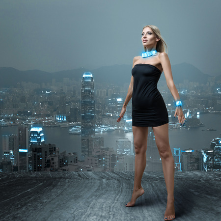 Futuristic fashion woman posing in small black dress at cityscape of night hongkong city Stock Photo