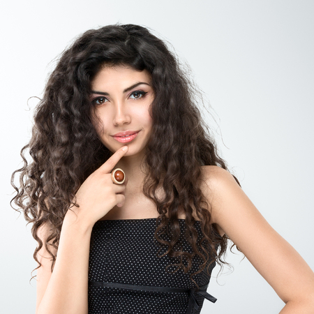 grey hair female: Young beautiful woman portrait with long curly hair posing in studio