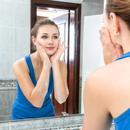 wash face: Young woman washing her face with clean water in bathroom