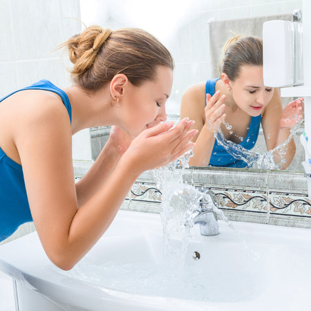 若い女性浴室のきれいな水で顔を洗った 写真素材