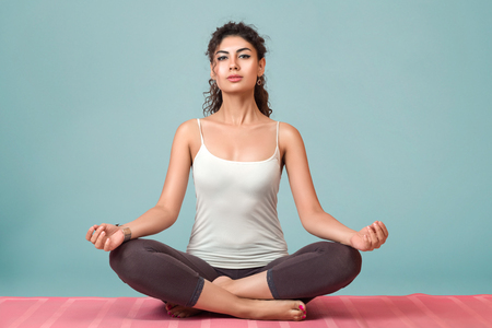 slim body: Young woman doing yoga and meditating in lotus position