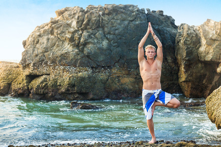 tree position: Young man doing yoga and meditating in tree position at sea beach