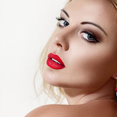 looking over shoulder: Studio portrait of young blonde woman looking over shoulder