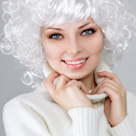 peruke: Woman in warm clothing with white wig against gray studio background Stock Photo