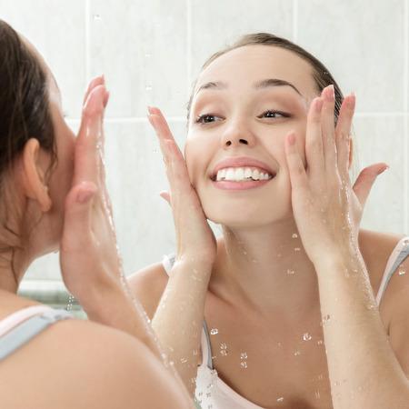 gesichter: Junge Frau, die ihr Gesicht mit klarem Wasser in Badezimmer