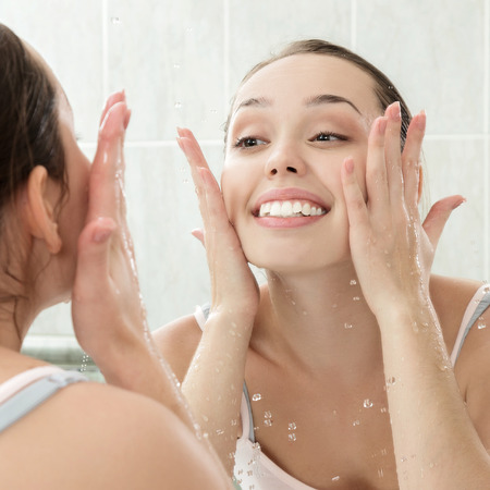 women body: Young woman washing her face with clean water in bathroom