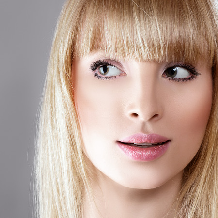 Beauty surprised blonde woman against gray background photo