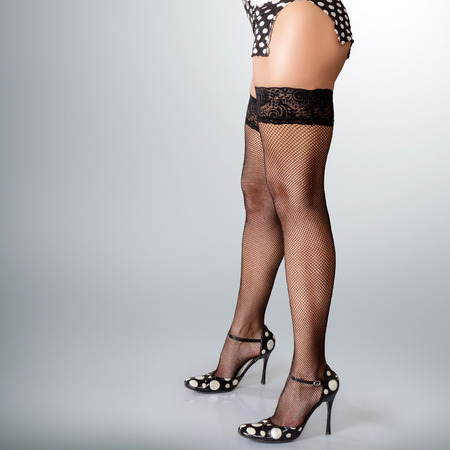 fishnet: Sexy long muscular female legs in high heels Stock Photo