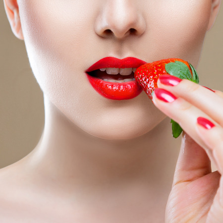 ripeness: Young woman face lips close-up eating red ripe strawberry