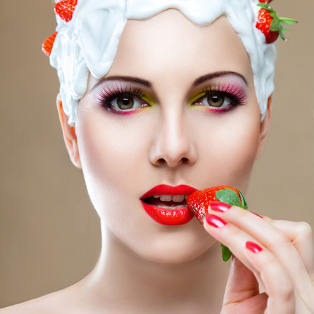 ripeness: Young woman with hairstyle made from milk eating red ripe strawberry