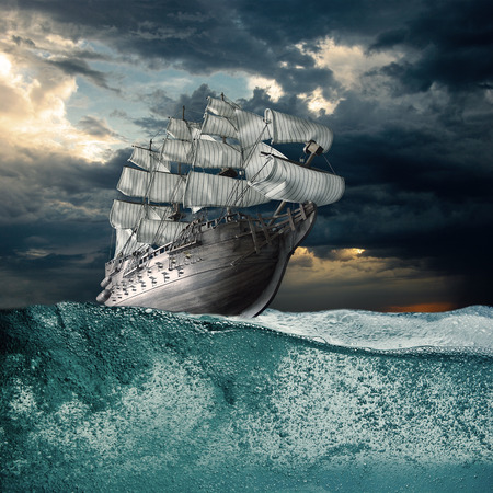 Sail ship in storm sea against heavy sunset clouds Stock Photo