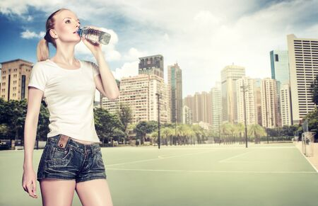 Young healthy woman drinking water while training outdoor photo
