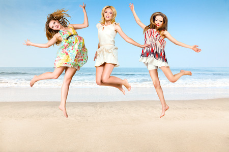 Group of young woman jumping on sea beach photo