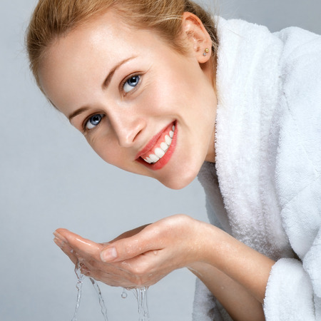 Mladá žena mytí obličeje s čistou vodou Reklamní fotografie