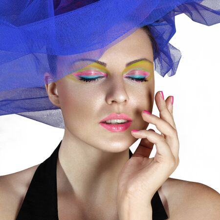 Beautiful young woman in blue fashionable hat touching face Stock Photo
