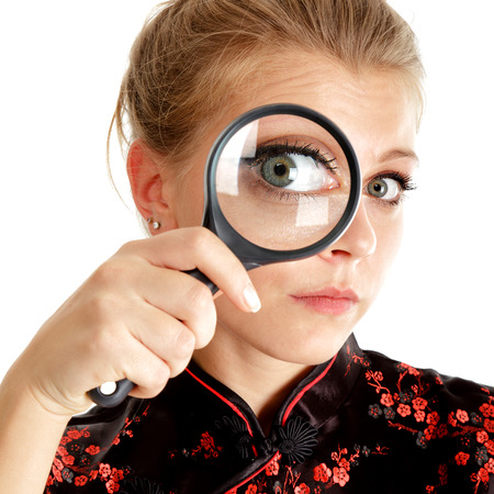 Young woman looking through a magnifying glass isolated over white photo
