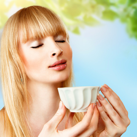 Young blonde woman with cup of herbal tea photo