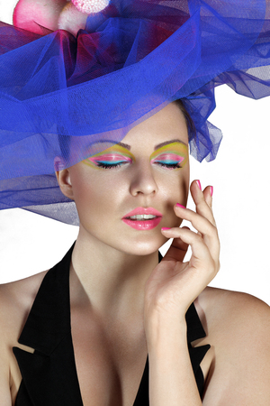 touching face: Beautiful young woman in blue fashionable hat touching face Stock Photo